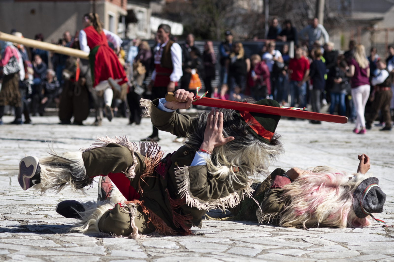Kukeri mummers perform simulated sword fights in Popintsi for Sirnitsa. One person inevitably is vanquished and falls dramatically on the ground, followed by the victor somersaulting over them. The kukeri dress as bears to chase away evil spirits.